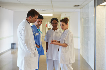 Group of medical staff talking in a relaxed moment in a hospital hall