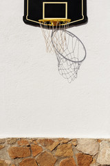 Basketball ring on white sunny wall