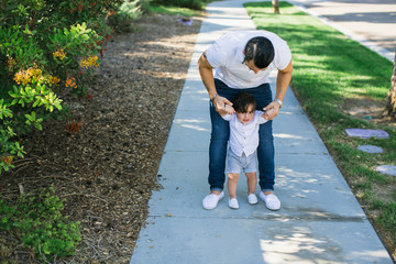 Young dad connecting with child on suburban sidewalk