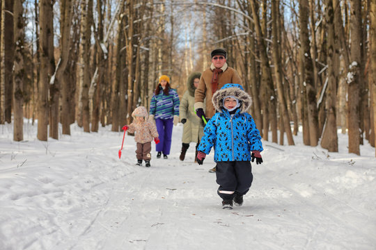 Kid running in winter park and have fun with family