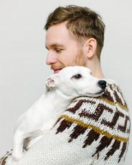 Dog holding head on shoulder of man