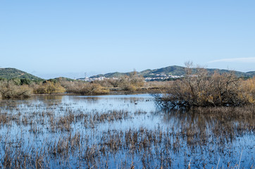 Landscape photography of a lake with a village of Menorca in the background.