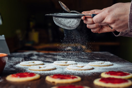 Woman's hands sifting sugar on shortbread cookies