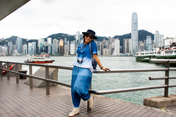 Travelers thai woman posing for take photo with view landscape and cityscape of Hong Kong island at Victoria Harbour pier