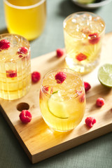 Fermented tea with raspberry and lime on wooden board.