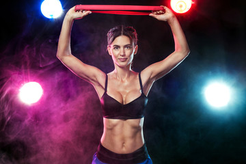 Fit sports woman athlete. Workout with bands or expander in gym with colorful bright blue and red lights.