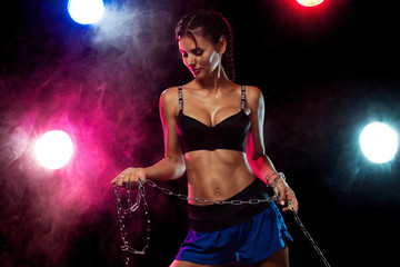 Muscular young fit sports woman athlete. Workout with chains on black background. Copy space for fitness nutrition ads.