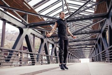 Male athlete jumping rope on the bridge
