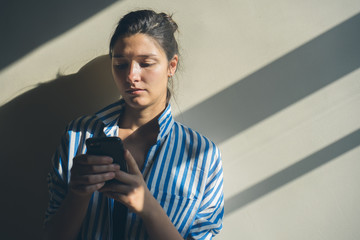 Portrait of a Young Woman at Home Checking Her Phone.