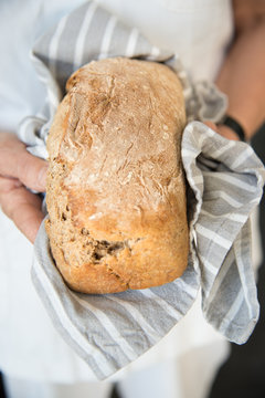 Woman holding a freshly made homemade bread on a kitchen towel