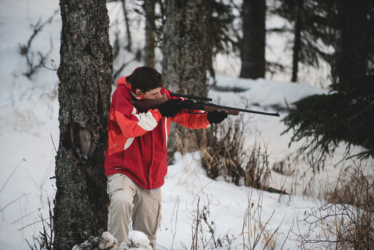 A teen boy at play with an air soft gun in the woods