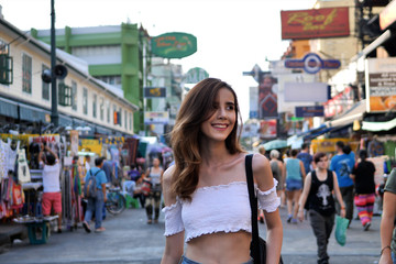 Beautiful young woman caucasian in city centre are walking Khaosan Road walking street in evening at Bangkok, Thailand. Happy female traveler and tourist concept..