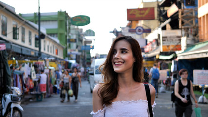 Young traveling women in city centre are walking Khaosan Road walking street in evening at Bangkok, Thailand. Happy female traveler and tourist concept.