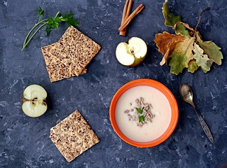 Apple cream soup in an orange bowl. Served with grain crackers and sunflower seeds