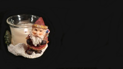 Burning candle and a small figure of Santa Claus on a black background. Horizontal image. Isolated