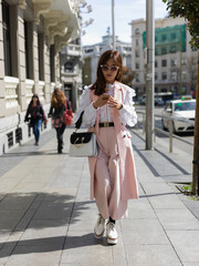 Trendy woman walking on street with phone