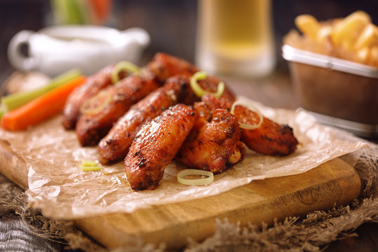 Roasted chicken wings served on a wooden board with glass of beer, french fries, carrot, celery and sause