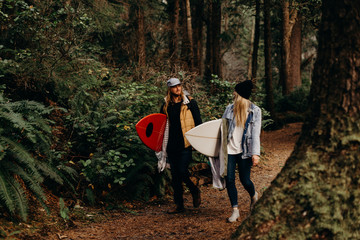 Surf couple walking through forest smiling