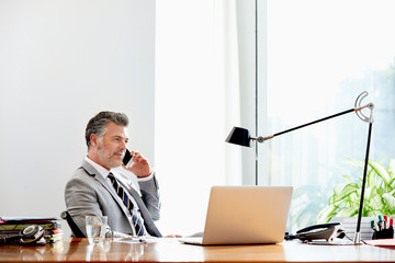 Thoughtful Executive Talking On Phone At Desk