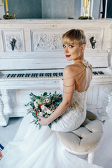 stylish bride with short hair sitting on a chair at home