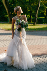Beautiful bride with a bouquet of flowers looking afar in a summer day