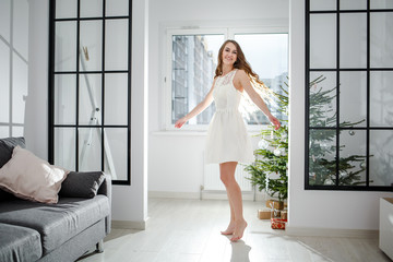 a young wife dances in a room next to a Christmas tree