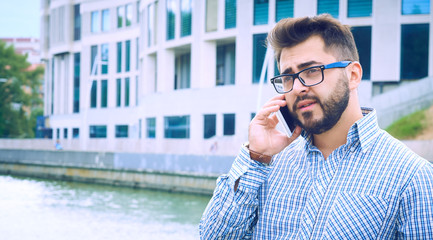 Handsome hipster modern businessman in glasses with beard walking in town and calling on mobile phone