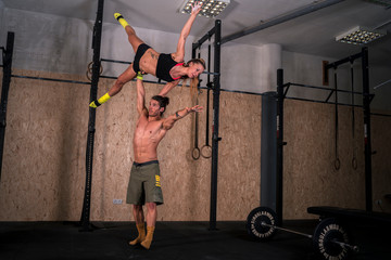 Male and female acrobats perform gymnastic yoga exercises in the gym