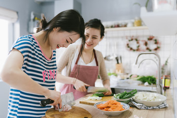 Young chinese women cooking at home