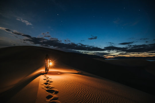 portrait of a woman with lantern walking on sand dunes at night