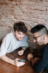 Men browsing smartphone in bar