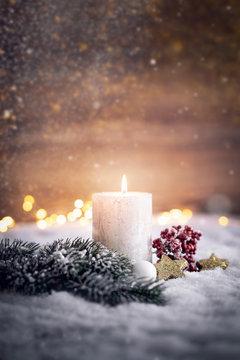 festliches Weihnachtsgesteck mit Kerze im Schnee