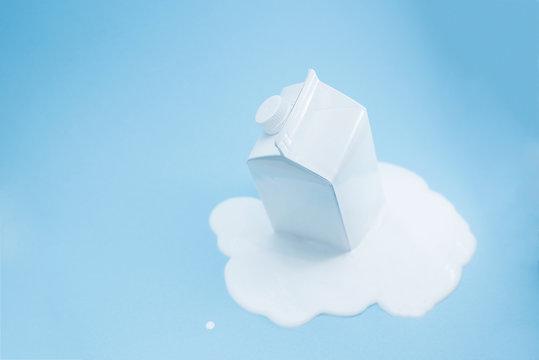 White milk carton melting on blue background