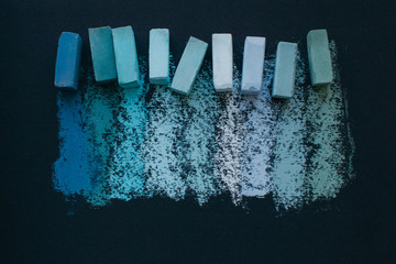 Assorted blue soft pastel chalks and it's swatches on black paper
