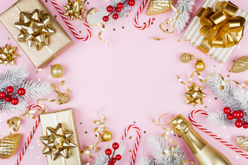 Christmas background with snowy fir tree, gift or present box, champagne and holiday decorations on pink pastel table top view. Greeting card with space for text. Flat lay.