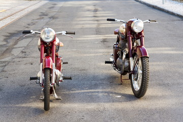Red vintage motorcycles Jawa 125 and Jawa 500 produced in former Czechoslovakia stand on road