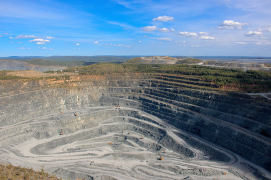 Aerial view industrial of opencast mining quarry with lots of machinery at work