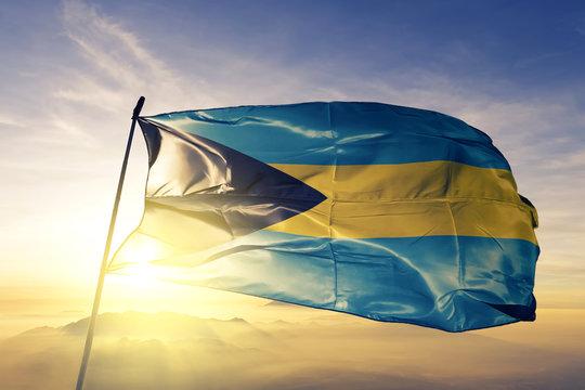 Bahamas Bahamian flag textile cloth fabric waving on the top sunrise mist fog