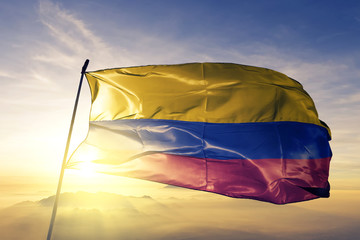Colombia Colombian flag textile cloth fabric waving on the top sunrise mist fog