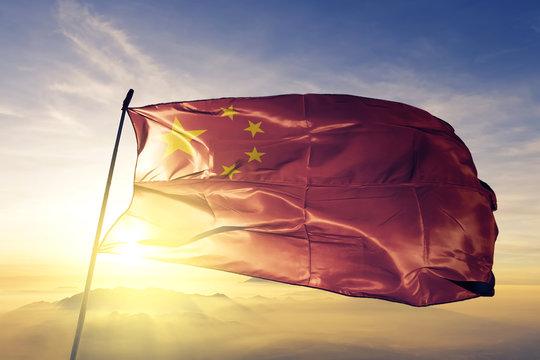 China Chinese flag textile cloth fabric waving on the top sunrise mist fog