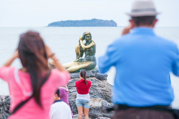 Tourists taking photos the Mermaid golden statue symbol of the Samila beach, inspired by the famous folk tale. Sea and island background. Songkhla, Thailand.