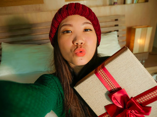 young beautiful and happy Asian American girl taking selfie picture with mobile phone holding Christmas gift box smiling cheerful and excited in winter beamy