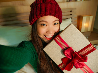 young beautiful and happy Asian American woman taking selfie picture with mobile phone holding Christmas gift box smiling cheerful and excited in winter beamy