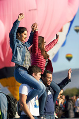 Group of friends having a happy time at a hot air balloon festival
