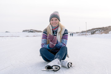 Cheerful woman with skates on ice
