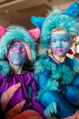 Portrait of Brother and Sister dressed up as colorful cats