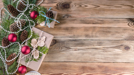 Web banner Christmas background. Christmas gifts, fir branches and cones on a wooden background