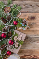 Christmas background. Christmas gifts, fir branches and cones on a wooden background. Vertical shot