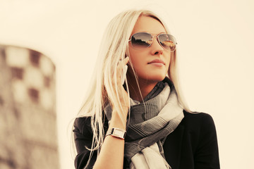Blond fashion business woman in sunglasses using cell phone outdoor