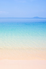 Peaceful summer, turquoise blue seawater and light blue sky, beautiful sand beach and gently waves, island background. Sunshine day. Thailand.